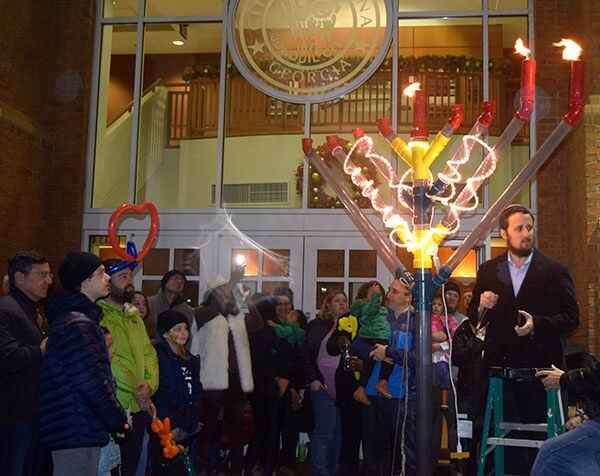 Rabbi Shmuel Wolf of Chabad of Cobb leads the prayer after lighting the Menorah on the second night of Chanukah in a cer...